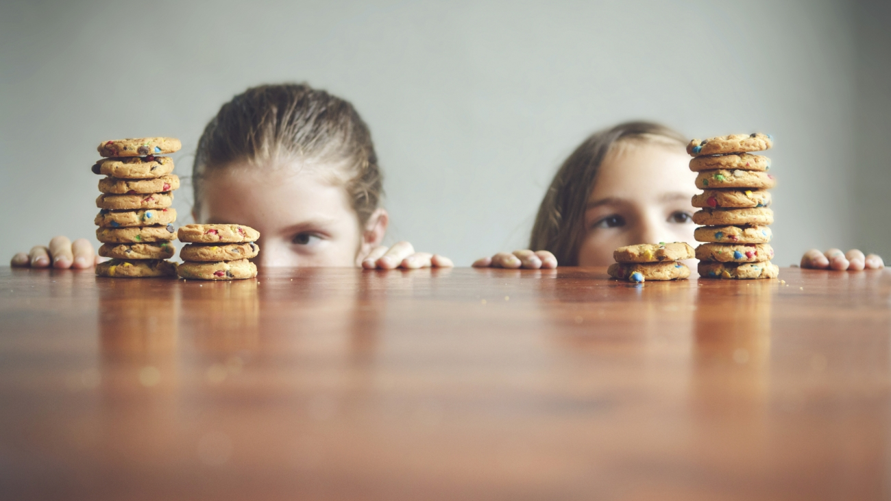 Caucasian girls staring at cookies on table