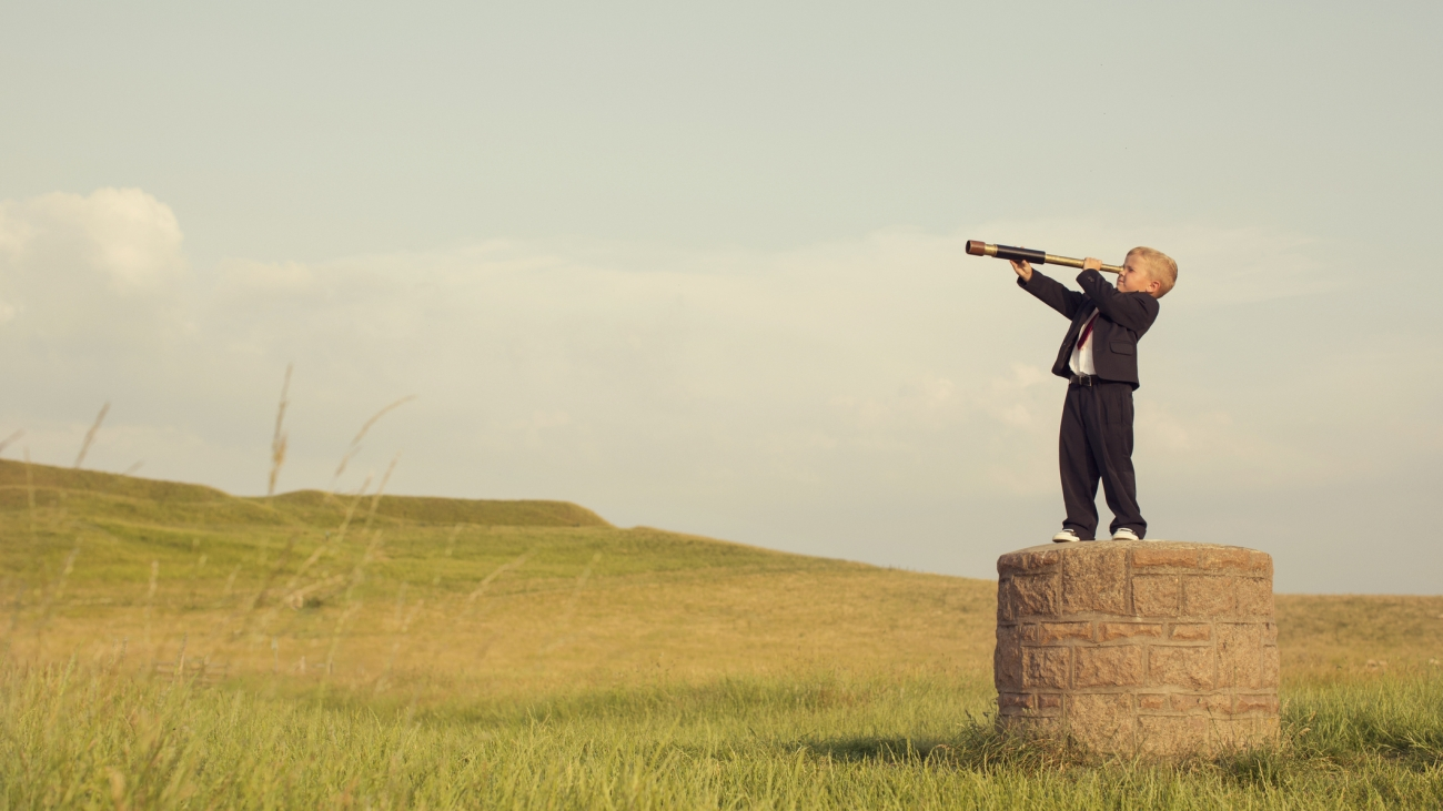 A young British boy in a business suit is standing on a pedestal looking through a hand-held telescope in the English countryside. He is looking for more business opportunities.